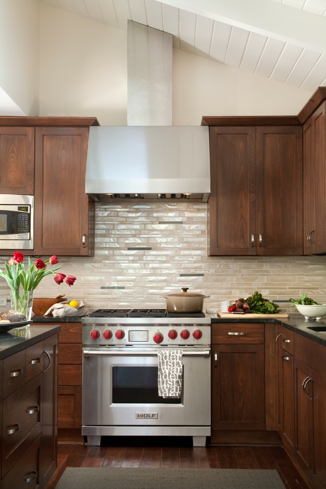 Inspiration for a large contemporary dark wood floor kitchen remodel in Santa Barbara with soapstone countertops, shaker cabinets, dark wood cabinets, beige backsplash, glass tile backsplash, stainless steel appliances and an island