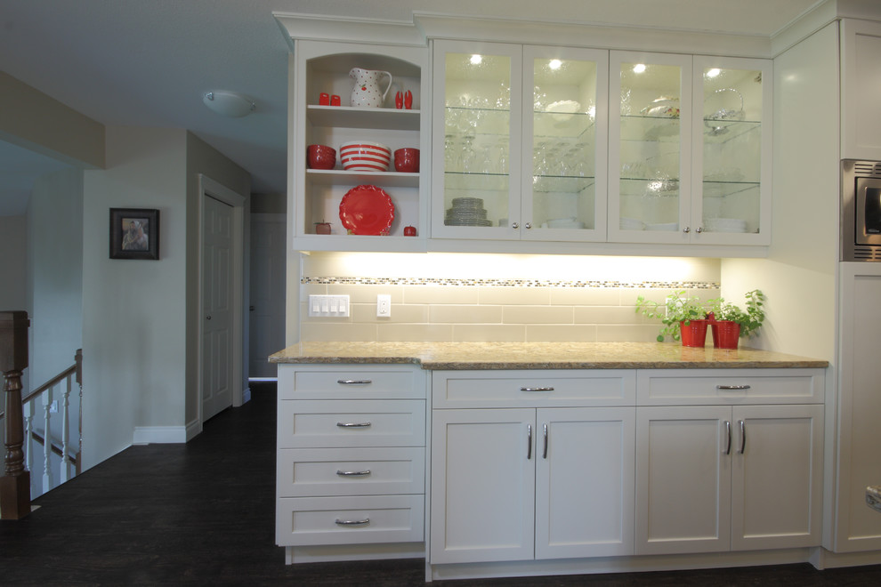 Example of a mid-sized trendy u-shaped dark wood floor and brown floor eat-in kitchen design in Other with an undermount sink, shaker cabinets, white cabinets, granite countertops, stainless steel appliances, an island and white backsplash