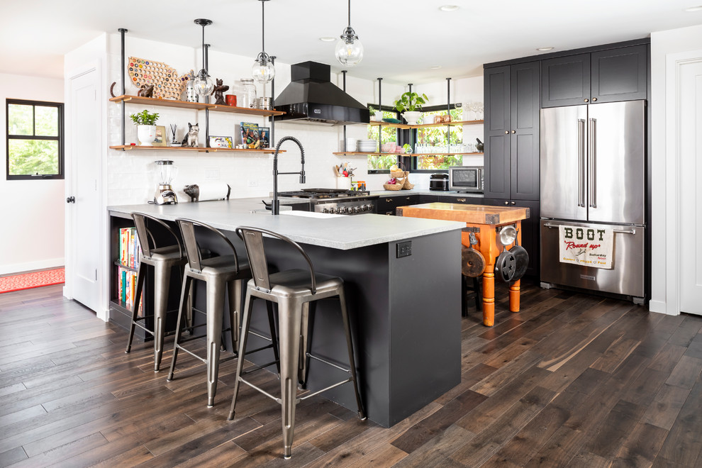 Kitchen - mid-sized contemporary u-shaped dark wood floor and brown floor kitchen idea in Seattle with a farmhouse sink, shaker cabinets, black cabinets, quartz countertops, white backsplash, porcelain backsplash, stainless steel appliances, a peninsula and gray countertops