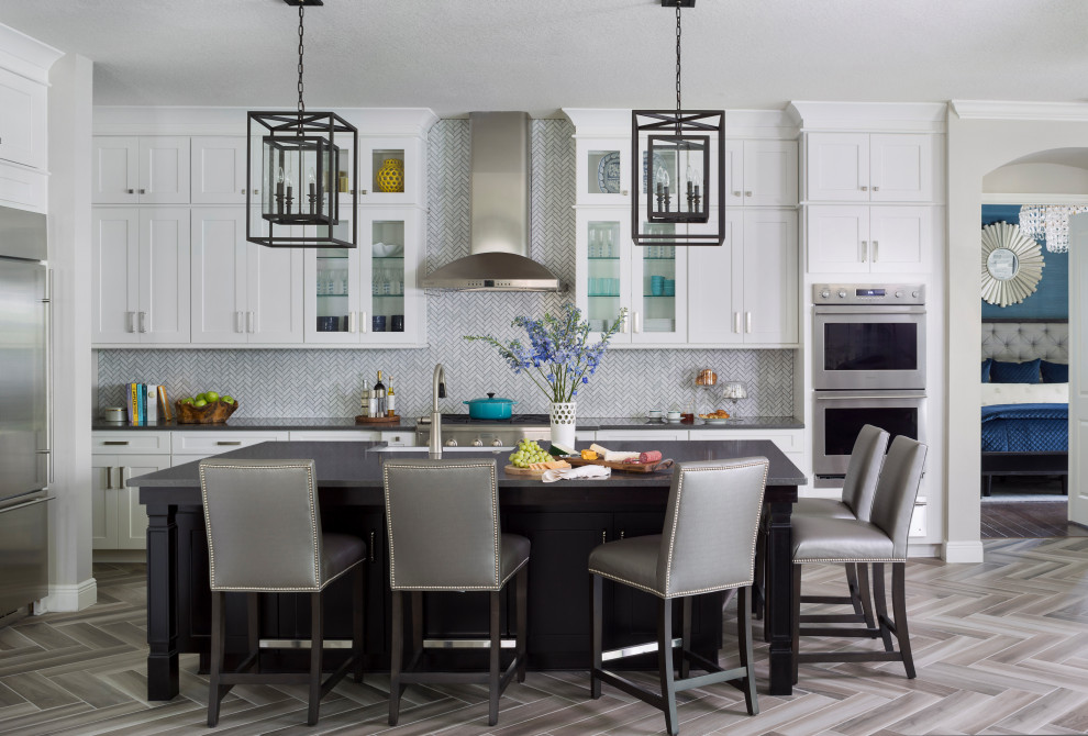 Inspiration for a large timeless l-shaped ceramic tile and gray floor open concept kitchen remodel in Tampa with a farmhouse sink, shaker cabinets, white cabinets, quartz countertops, white backsplash, marble backsplash, stainless steel appliances, an island and black countertops