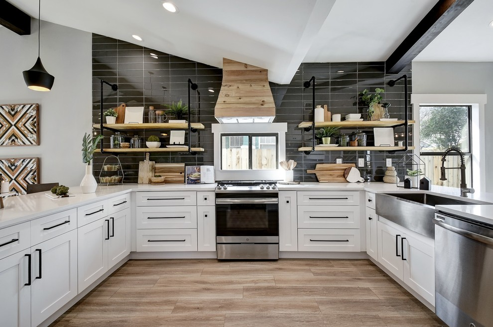 Example of a mid-sized trendy u-shaped brown floor kitchen design in Austin with a farmhouse sink, shaker cabinets, white cabinets, black backsplash, stainless steel appliances and white countertops