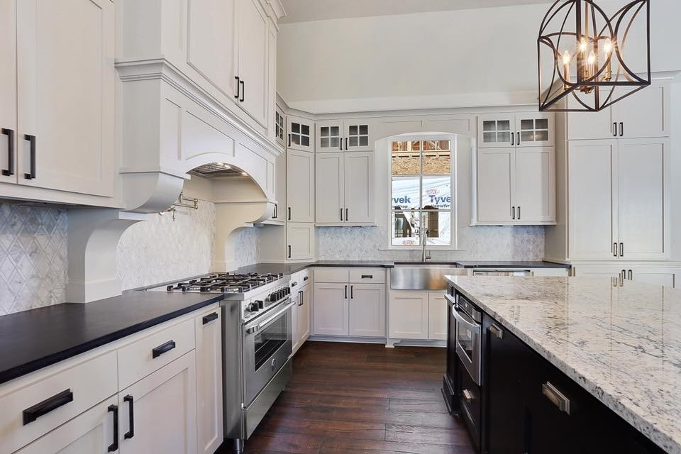 Inspiration for a large transitional medium tone wood floor and brown floor kitchen remodel in New Orleans with a farmhouse sink, recessed-panel cabinets, white cabinets, granite countertops, gray backsplash, mosaic tile backsplash, stainless steel appliances and an island