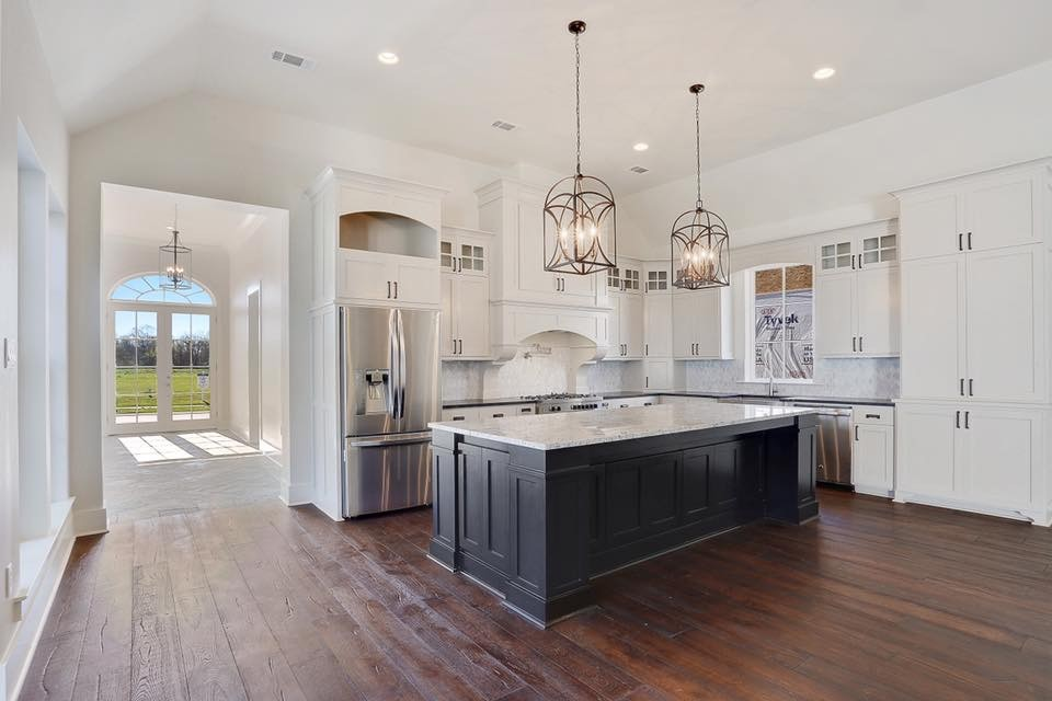 Example of a large transitional l-shaped medium tone wood floor and brown floor kitchen design in New Orleans with a farmhouse sink, recessed-panel cabinets, white cabinets, granite countertops, gray backsplash, mosaic tile backsplash, stainless steel appliances and an island