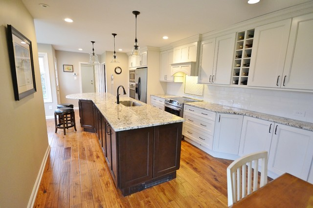 Inspiration for a large transitional l-shaped medium tone wood floor and brown floor eat-in kitchen remodel in Philadelphia with an undermount sink, recessed-panel cabinets, white cabinets, granite countertops, white backsplash, subway tile backsplash, stainless steel appliances, an island and multicolored countertops