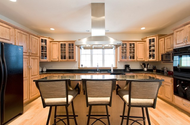 Example of a transitional light wood floor kitchen design in Other with a double-bowl sink, raised-panel cabinets, light wood cabinets, granite countertops, black appliances and an island