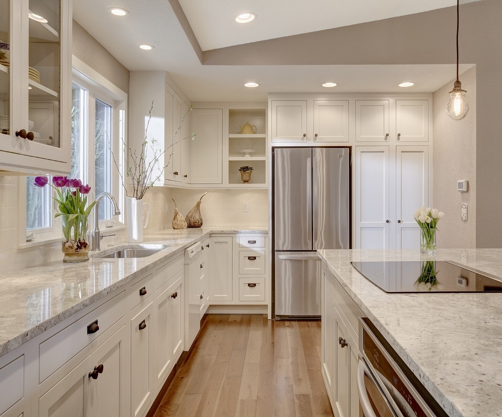 Kitchen - transitional l-shaped kitchen idea in Seattle with an undermount sink, shaker cabinets, white cabinets, stainless steel appliances and an island