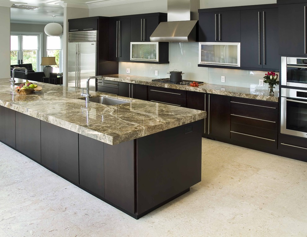 Example of a trendy galley kitchen design in Wilmington with stainless steel appliances, an undermount sink, flat-panel cabinets, dark wood cabinets and glass sheet backsplash