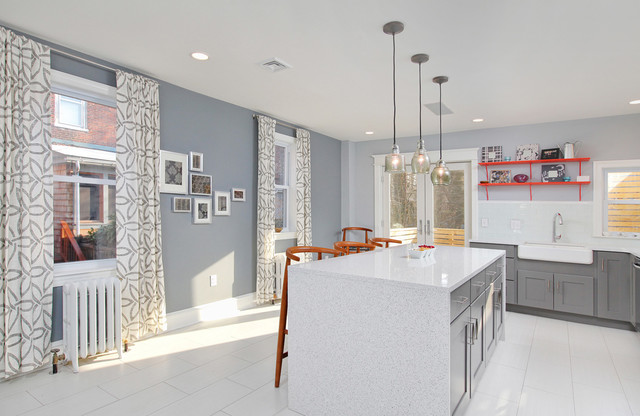 Inspiration for a large modern l-shaped porcelain floor eat-in kitchen remodel in Philadelphia with a farmhouse sink, gray cabinets, white backsplash, an island, shaker cabinets, quartz countertops, subway tile backsplash and stainless steel appliances