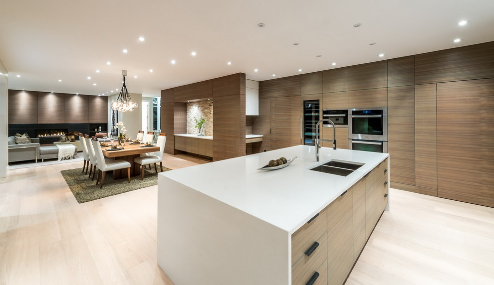 Inspiration for a large contemporary l-shaped light wood floor open concept kitchen remodel in Vancouver with an undermount sink, flat-panel cabinets, light wood cabinets, solid surface countertops, white backsplash, stone slab backsplash, stainless steel appliances and an island