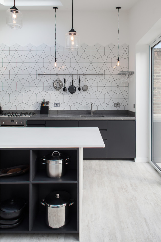Inspiration for a contemporary kitchen remodel in London with an undermount sink, flat-panel cabinets, black cabinets, white backsplash and an island