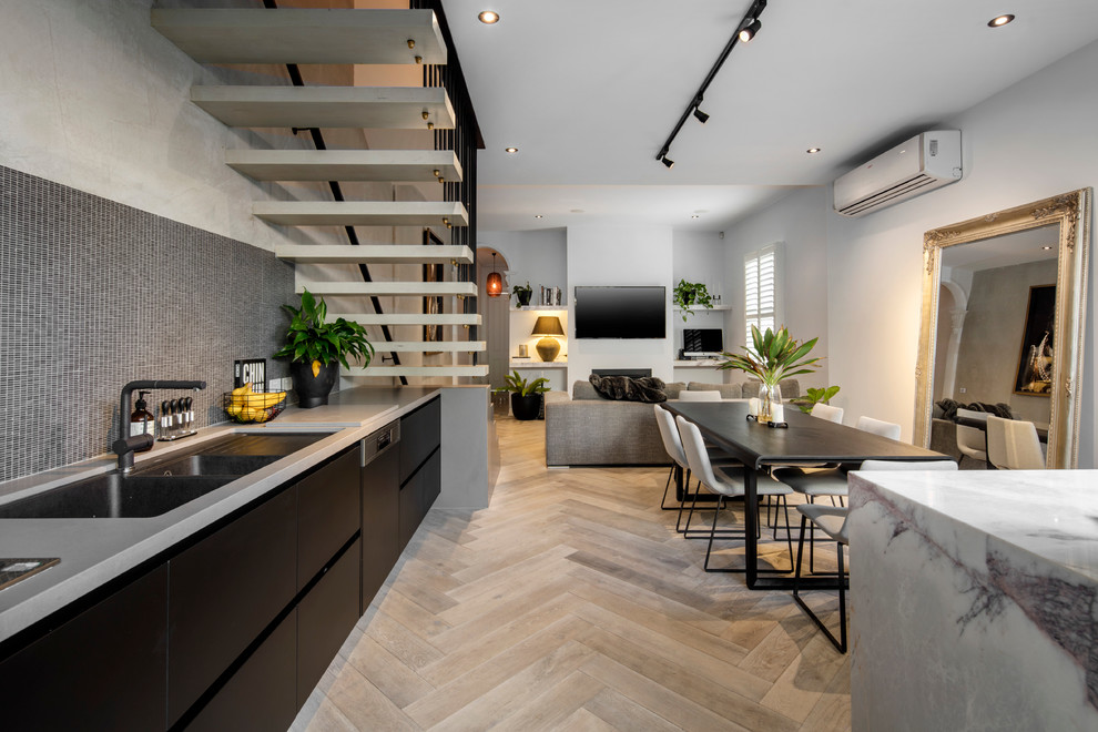 Open concept kitchen - mid-sized contemporary single-wall light wood floor open concept kitchen idea in Melbourne with an undermount sink, black cabinets, marble countertops, black backsplash, mosaic tile backsplash, stainless steel appliances and an island