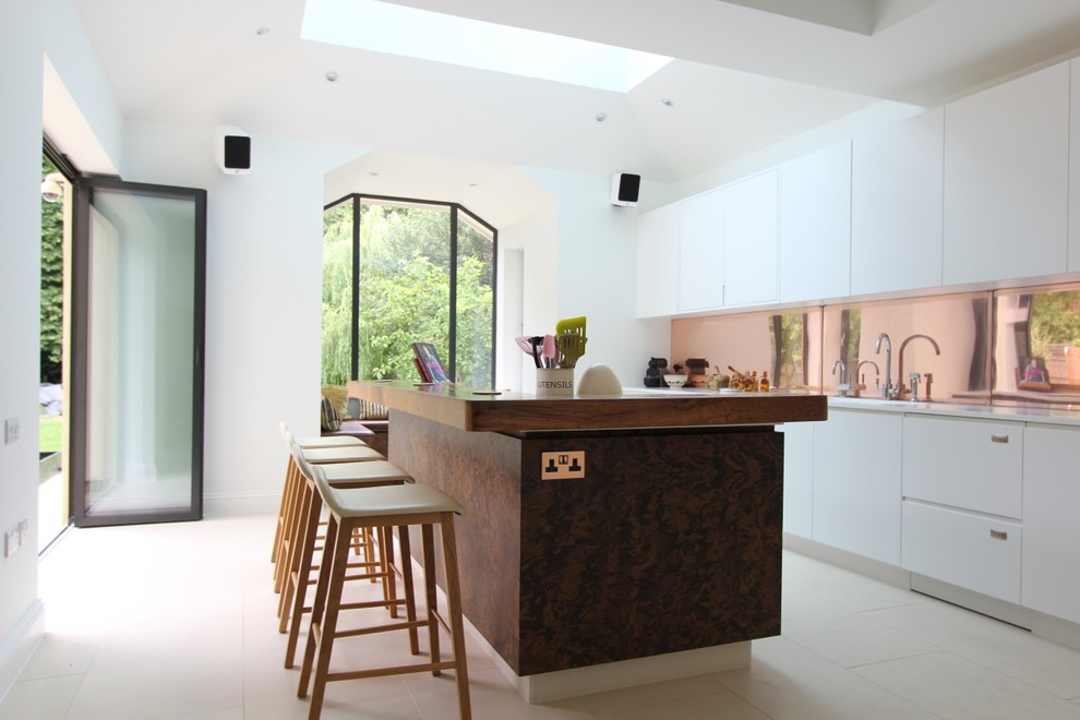 Example of a large trendy single-wall ceramic tile open concept kitchen design in London with an undermount sink, flat-panel cabinets, dark wood cabinets, wood countertops, stainless steel appliances and an island