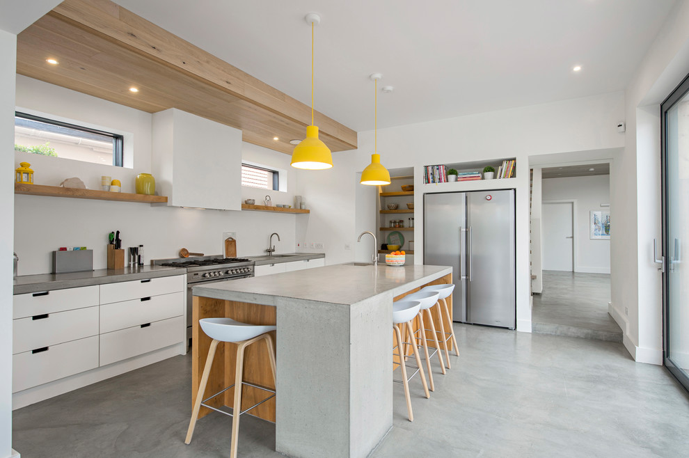 Kitchen - mid-sized industrial single-wall concrete floor and gray floor kitchen idea in Dublin with flat-panel cabinets, white cabinets, concrete countertops, white backsplash, an island and stainless steel appliances