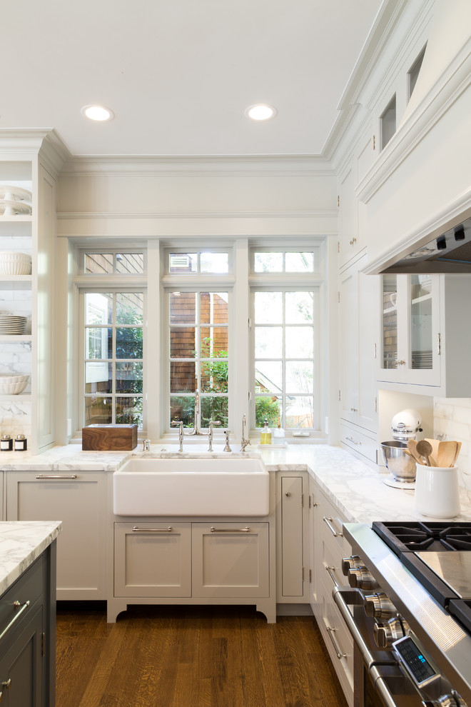 Example of a large beach style medium tone wood floor eat-in kitchen design in San Francisco with a farmhouse sink, open cabinets, white backsplash, stainless steel appliances and an island