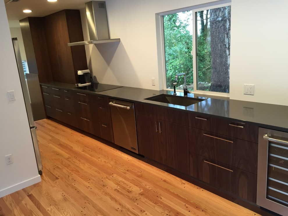 Inspiration for a mid-century modern galley medium tone wood floor eat-in kitchen remodel in Portland with flat-panel cabinets, dark wood cabinets, stainless steel appliances, no island, an undermount sink and quartz countertops