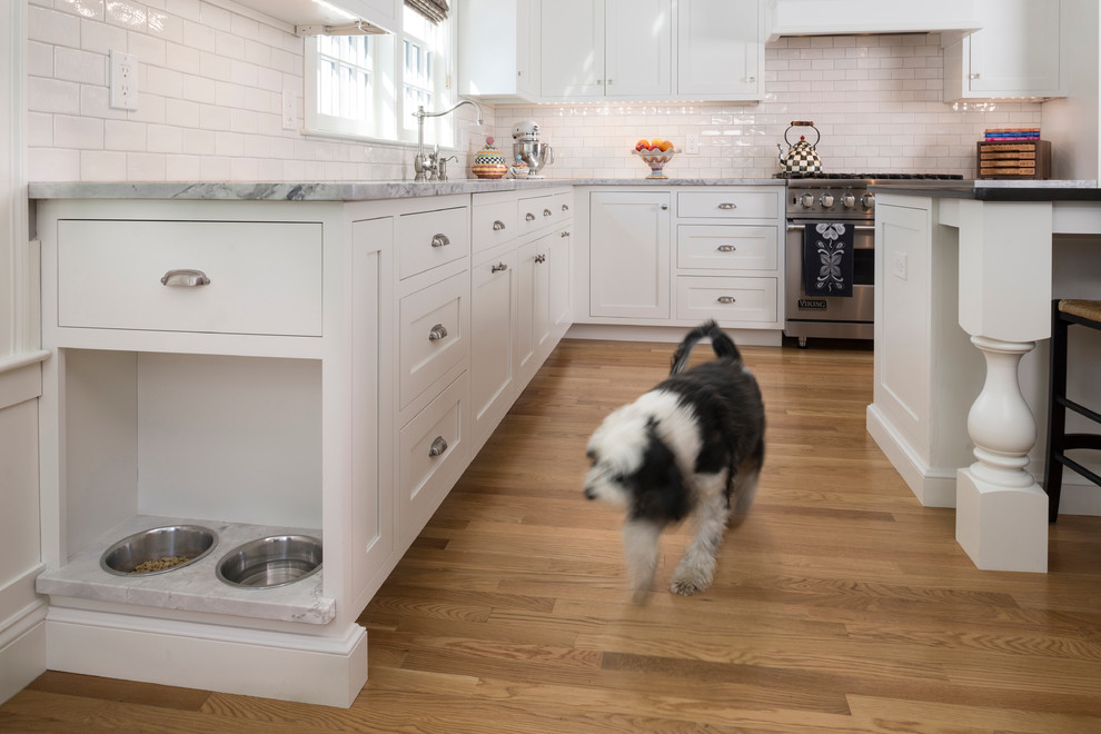 Inspiration for a large timeless l-shaped medium tone wood floor eat-in kitchen remodel in Boston with a single-bowl sink, white cabinets, quartzite countertops, white backsplash, ceramic backsplash, stainless steel appliances and an island
