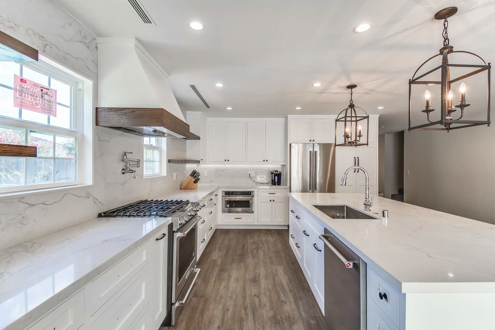 Mid-sized trendy u-shaped porcelain tile and brown floor eat-in kitchen photo in Orange County with an undermount sink, recessed-panel cabinets, white cabinets, quartz countertops, white backsplash, stone slab backsplash, stainless steel appliances, an island and white countertops