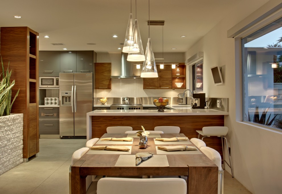 Inspiration for a mid-sized mid-century modern l-shaped concrete floor eat-in kitchen remodel in Los Angeles with flat-panel cabinets, medium tone wood cabinets, white backsplash, stainless steel appliances and a peninsula