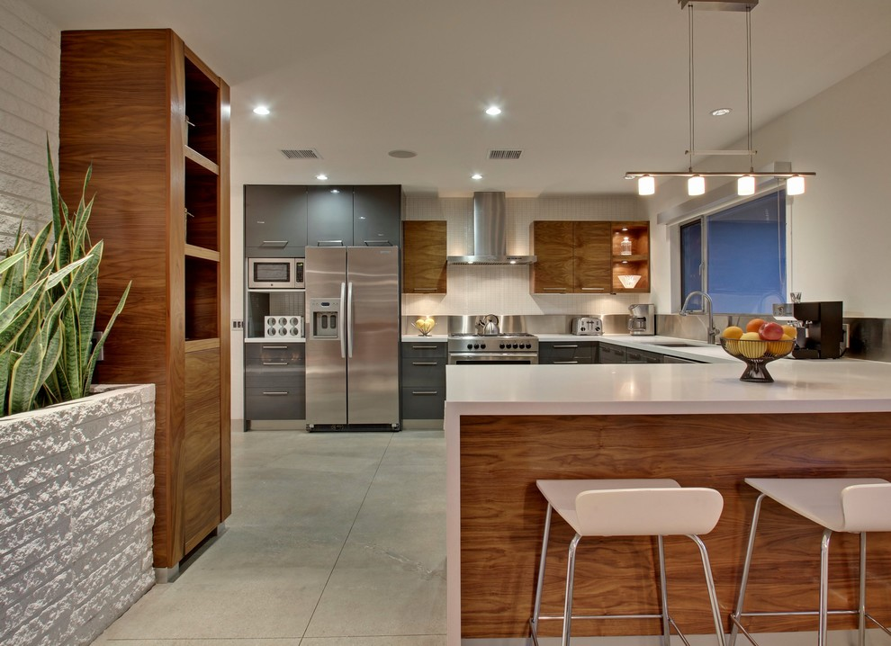 Example of a large mid-century modern u-shaped eat-in kitchen design in Los Angeles with an undermount sink, flat-panel cabinets, gray cabinets, metallic backsplash, stainless steel appliances and an island