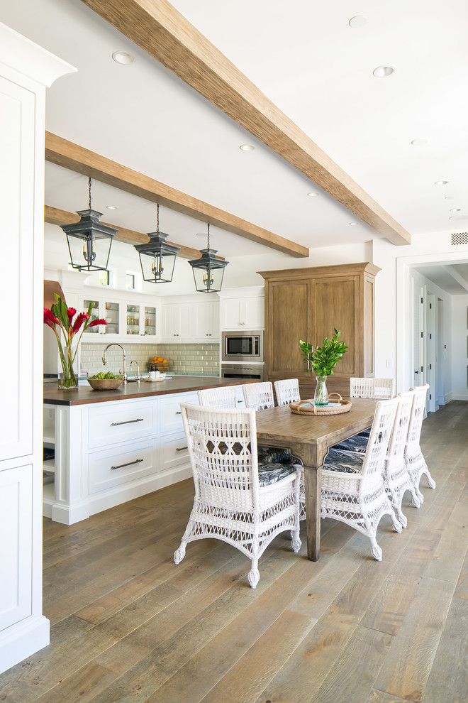 Eat-in kitchen - large tropical u-shaped medium tone wood floor and brown floor eat-in kitchen idea in Orange County with a double-bowl sink, shaker cabinets, white cabinets, wood countertops, white backsplash, subway tile backsplash, stainless steel appliances, an island and brown countertops