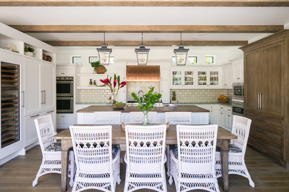 Inspiration for a large tropical u-shaped medium tone wood floor and brown floor eat-in kitchen remodel in Orange County with shaker cabinets, white cabinets, wood countertops, subway tile backsplash, stainless steel appliances, an island, brown countertops and beige backsplash