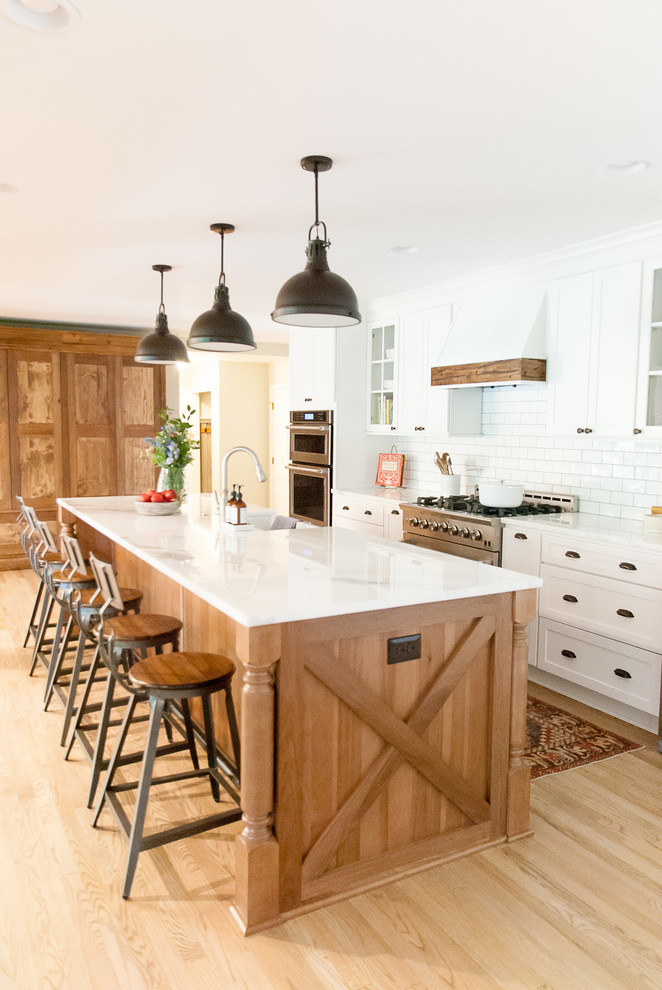 Inspiration for a farmhouse galley light wood floor and beige floor kitchen remodel in Houston with shaker cabinets, an island, white cabinets, white backsplash, subway tile backsplash and stainless steel appliances