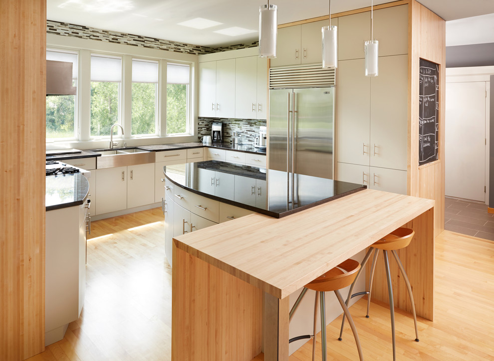 Trendy u-shaped medium tone wood floor kitchen photo in Minneapolis with a farmhouse sink, flat-panel cabinets, white cabinets, multicolored backsplash, stainless steel appliances and an island