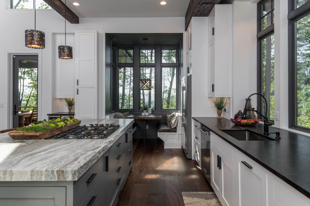 Inspiration for a large rustic l-shaped dark wood floor and brown floor eat-in kitchen remodel in Other with an undermount sink, shaker cabinets, white cabinets, granite countertops, white backsplash, window backsplash, stainless steel appliances, an island and black countertops