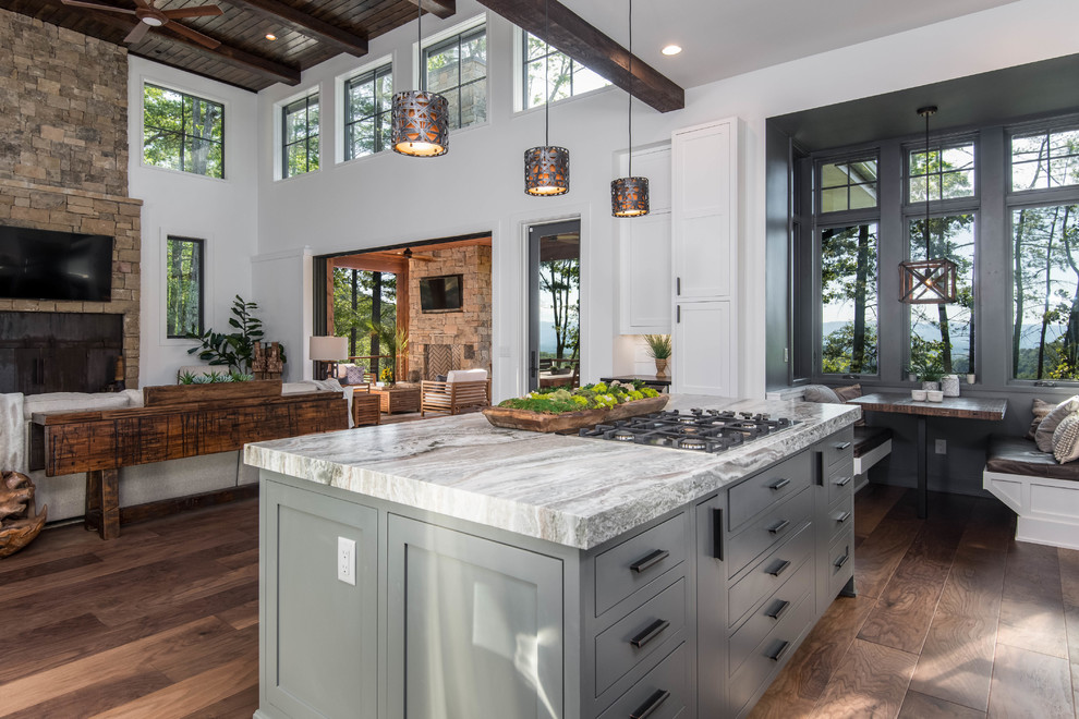 Large mountain style dark wood floor and brown floor open concept kitchen photo in Other with an undermount sink, shaker cabinets, white cabinets, granite countertops, white backsplash, window backsplash, stainless steel appliances, an island and black countertops
