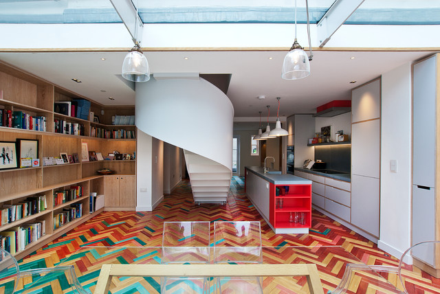 Inspiration for a contemporary galley open plan kitchen in London with a belfast sink, flat-panel cabinets, grey cabinets, concrete worktops, light hardwood flooring and an island.