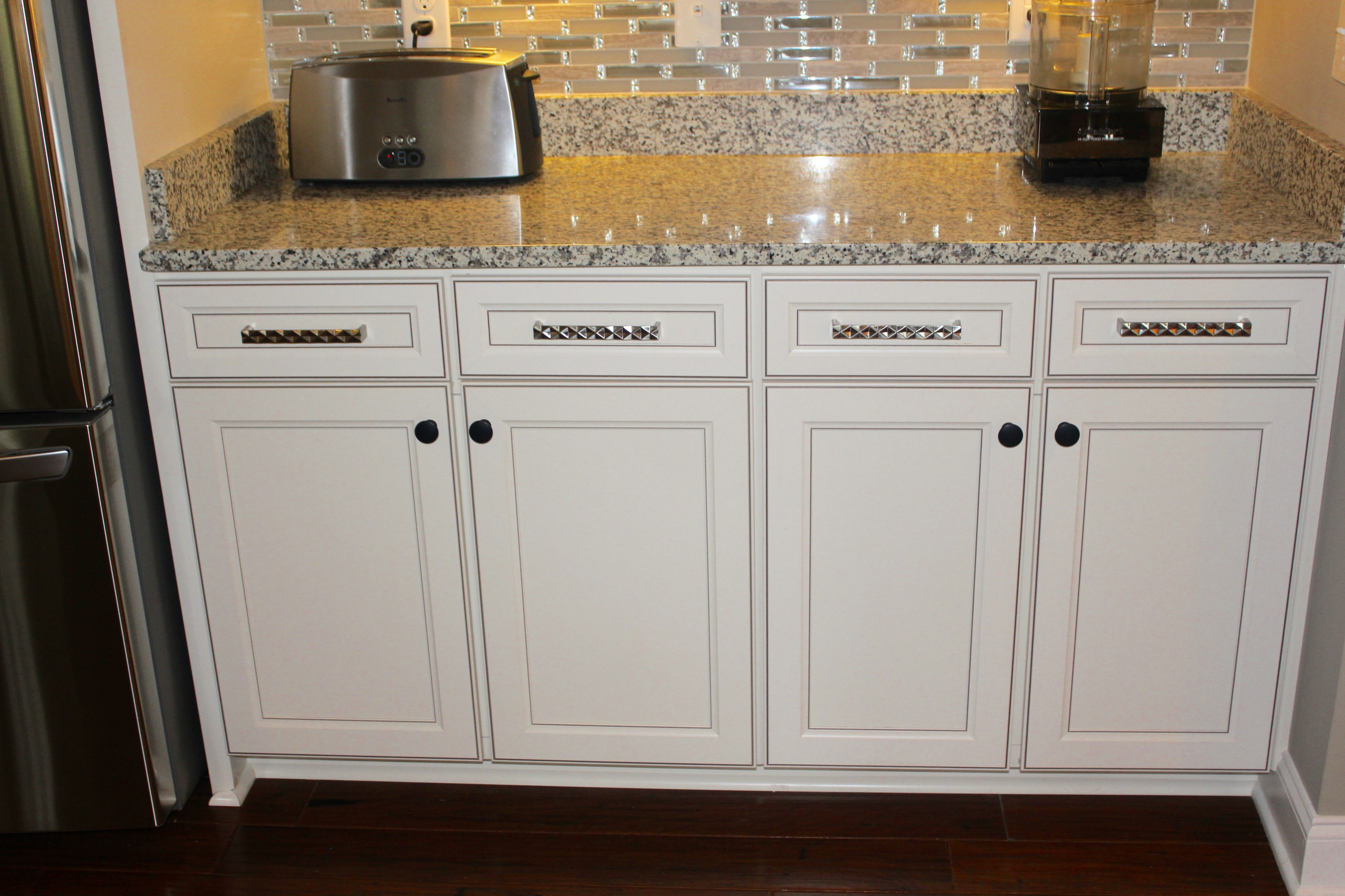 Oversized brushed nickel pulls are combined with black knobs