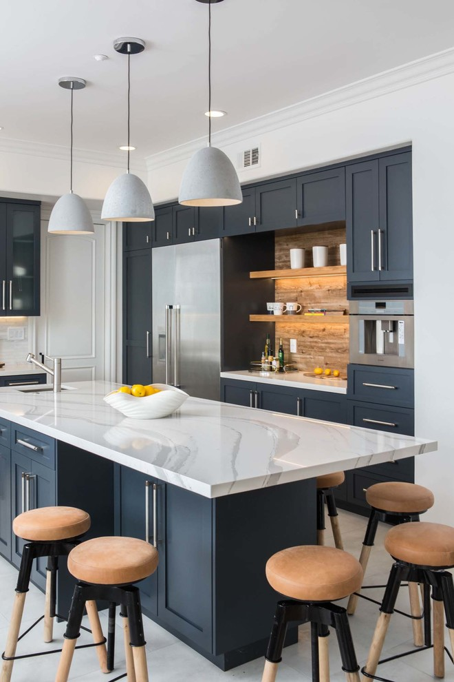 Example of a transitional gray floor kitchen design in Los Angeles with an undermount sink, shaker cabinets, black cabinets, an island, white countertops and brown backsplash