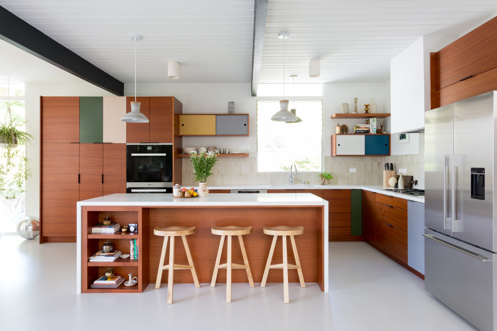 Inspiration for a mid-century modern l-shaped gray floor kitchen remodel in Los Angeles with an undermount sink, flat-panel cabinets, dark wood cabinets, beige backsplash, stainless steel appliances and an island