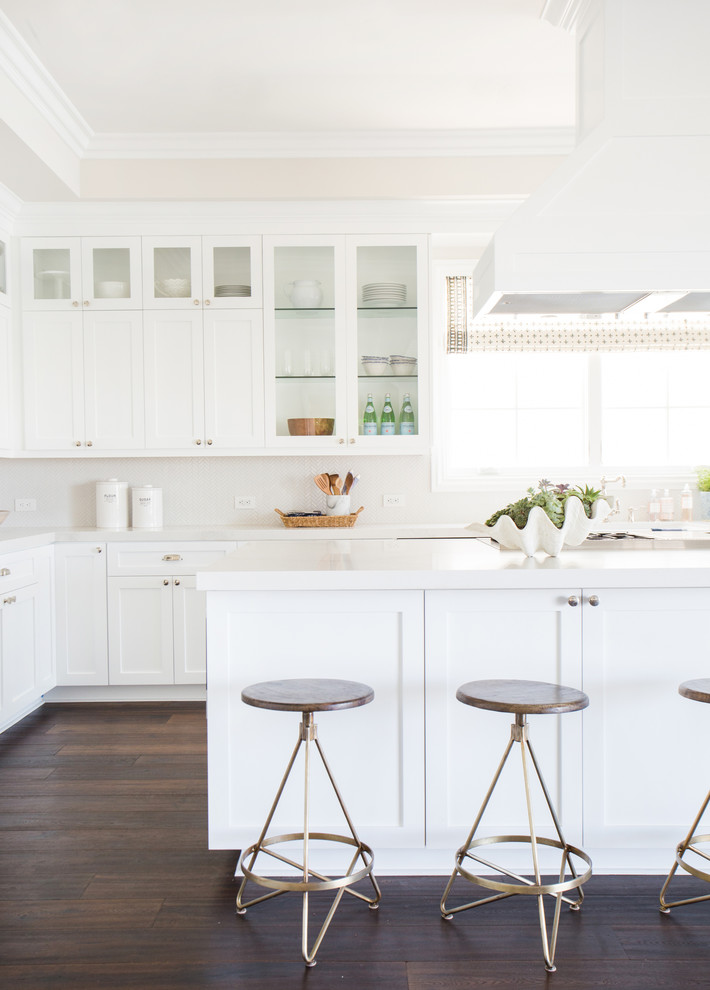 Example of a transitional u-shaped dark wood floor open concept kitchen design in Los Angeles with a farmhouse sink, flat-panel cabinets, white cabinets, white backsplash and stainless steel appliances