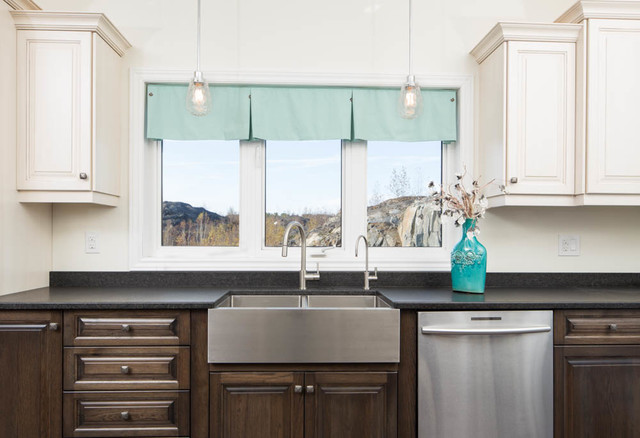 Example of a large eclectic single-wall enclosed kitchen design in Toronto with a farmhouse sink, raised-panel cabinets, dark wood cabinets, soapstone countertops, stainless steel appliances and an island