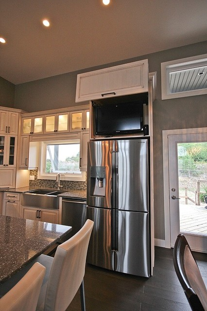 Enclosed kitchen - large transitional l-shaped dark wood floor and brown floor enclosed kitchen idea in Toronto with a farmhouse sink, raised-panel cabinets, white cabinets, limestone countertops, multicolored backsplash, mosaic tile backsplash, stainless steel appliances and an island
