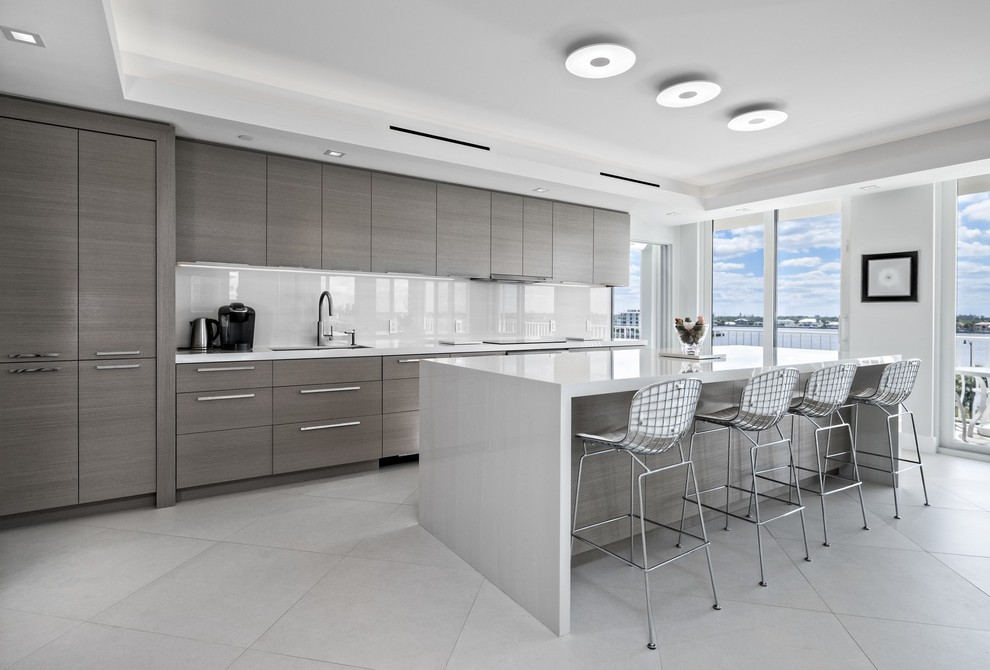Trendy galley gray floor kitchen photo in Miami with an undermount sink, flat-panel cabinets, gray cabinets, white backsplash, paneled appliances, an island and white countertops