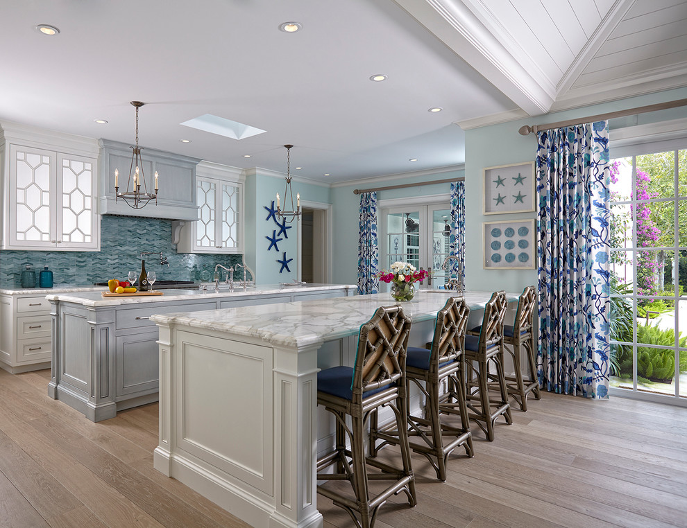 Example of a beach style single-wall light wood floor open concept kitchen design in Miami with white cabinets, marble countertops, blue backsplash, mosaic tile backsplash, two islands and recessed-panel cabinets