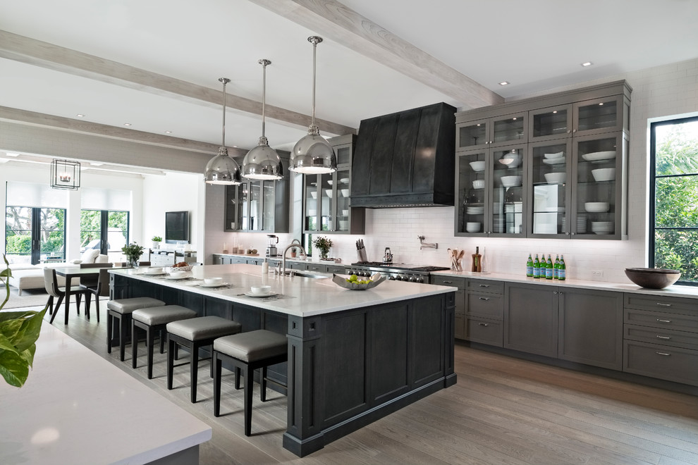 Inspiration for a transitional galley medium tone wood floor and brown floor kitchen remodel in Miami with an undermount sink, shaker cabinets, gray cabinets, white backsplash, stainless steel appliances, an island and white countertops