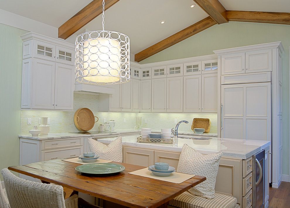 Example of a classic l-shaped medium tone wood floor eat-in kitchen design in Orlando with recessed-panel cabinets, white cabinets, paneled appliances, white backsplash and an island