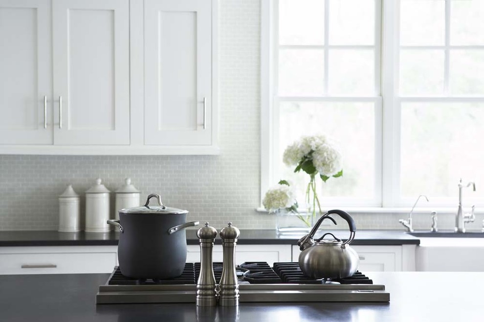 Eat-in kitchen - large traditional u-shaped eat-in kitchen idea in Charleston with a farmhouse sink, shaker cabinets, white cabinets, granite countertops, white backsplash, glass tile backsplash, stainless steel appliances and an island