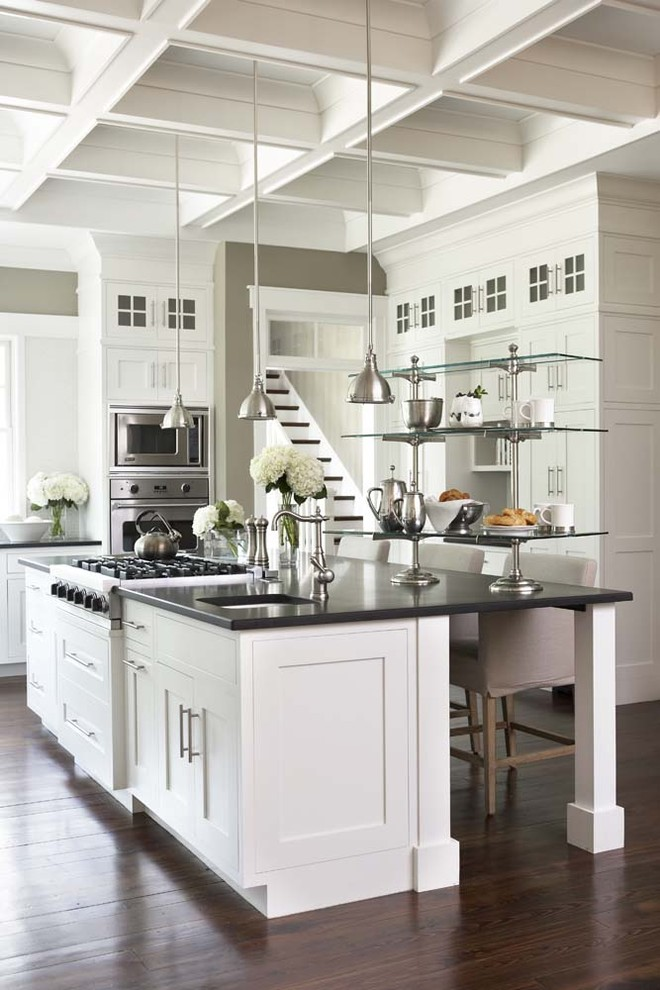 Open concept kitchen - large traditional u-shaped dark wood floor open concept kitchen idea in Charleston with stainless steel appliances, shaker cabinets, an island, granite countertops, an undermount sink and black countertops