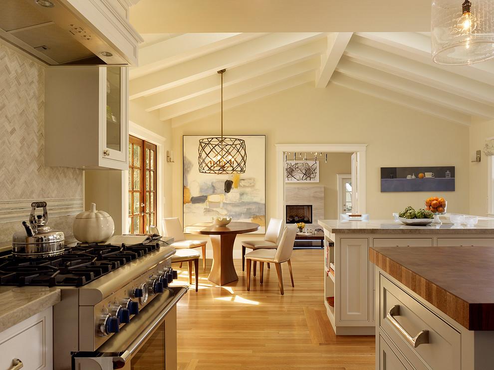 Diseño de cocina clásica renovada, grande, con electrodomésticos de acero inoxidable, encimera de madera, salpicadero verde, armarios con paneles empotrados, puertas de armario blancas, salpicadero de azulejos de piedra, suelo de madera en tonos medios, una isla y suelo marrón