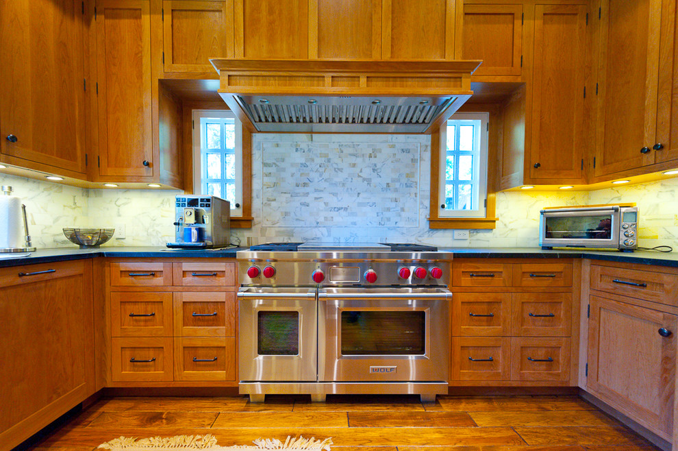 Inspiration for a mid-sized timeless u-shaped dark wood floor and brown floor enclosed kitchen remodel in San Francisco with a farmhouse sink, shaker cabinets, medium tone wood cabinets, soapstone countertops, white backsplash, marble backsplash, stainless steel appliances and no island