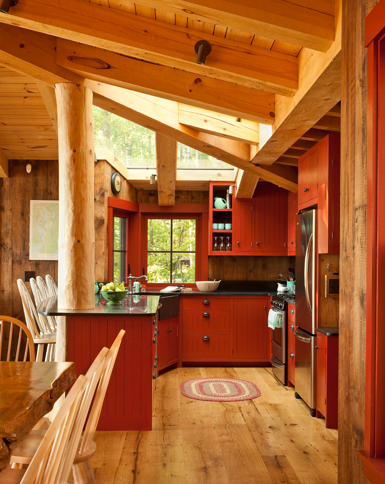 Kitchen - rustic u-shaped medium tone wood floor kitchen idea in Portland Maine with a farmhouse sink, red cabinets, soapstone countertops, stainless steel appliances and window backsplash