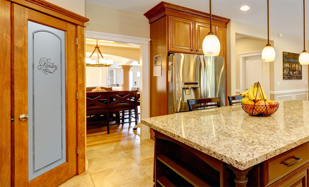 Example of a mid-sized arts and crafts l-shaped kitchen pantry design in Other with raised-panel cabinets, medium tone wood cabinets, granite countertops, beige backsplash, ceramic backsplash, stainless steel appliances and an island