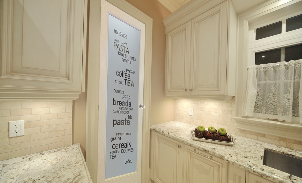 Mid-sized l-shaped kitchen pantry photo in Other with raised-panel cabinets, medium tone wood cabinets, granite countertops, beige backsplash, ceramic backsplash, stainless steel appliances and an island