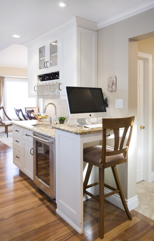 Elegant kitchen photo in Toronto with glass-front cabinets and granite countertops