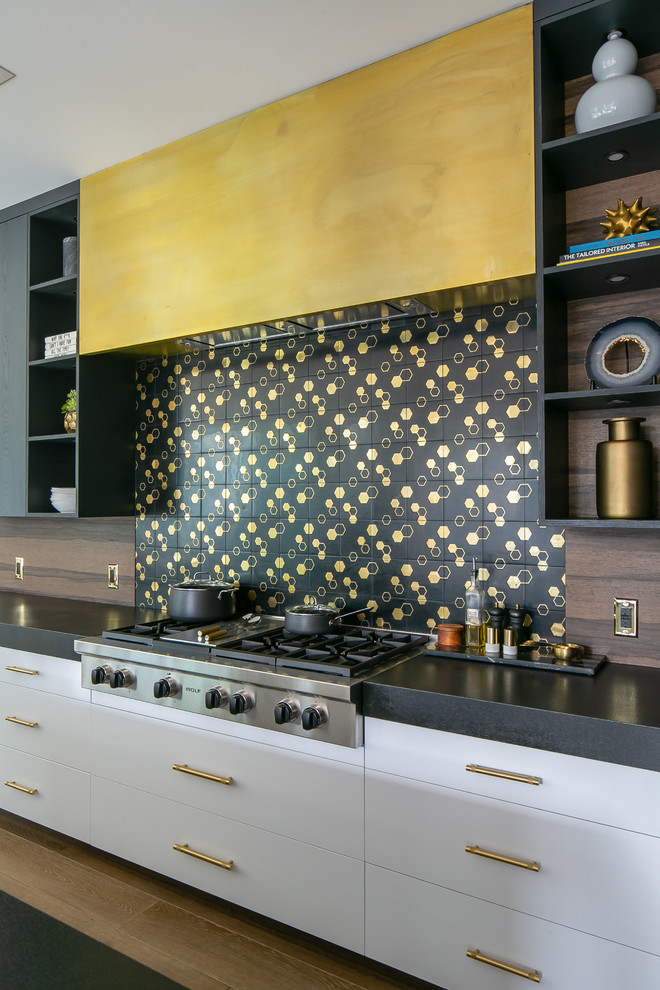Inspiration for a large contemporary medium tone wood floor and brown floor kitchen remodel in Orange County with flat-panel cabinets, black cabinets, black backsplash, an island and black countertops