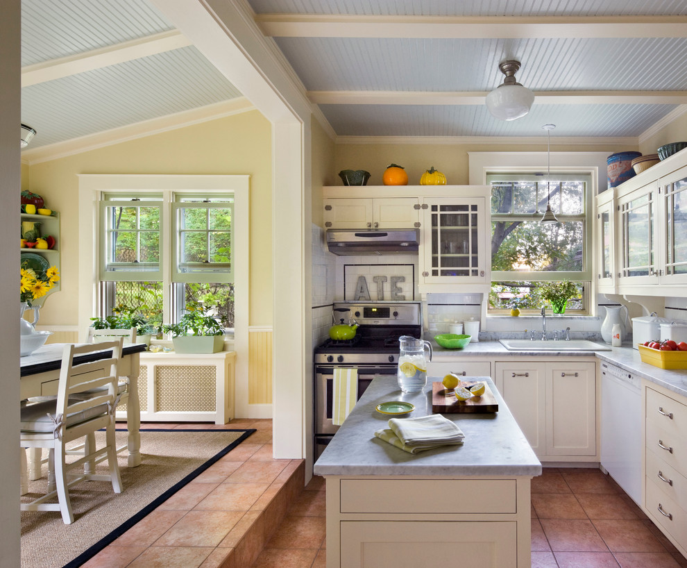 Example of a classic l-shaped eat-in kitchen design in New York with a drop-in sink, shaker cabinets, white cabinets, white backsplash, subway tile backsplash, stainless steel appliances and an island